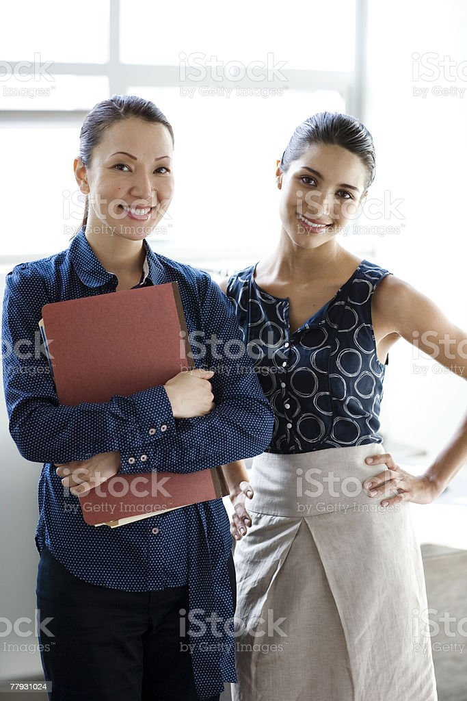 Two businesswomen standing indoors smiling royalty-free stock photo