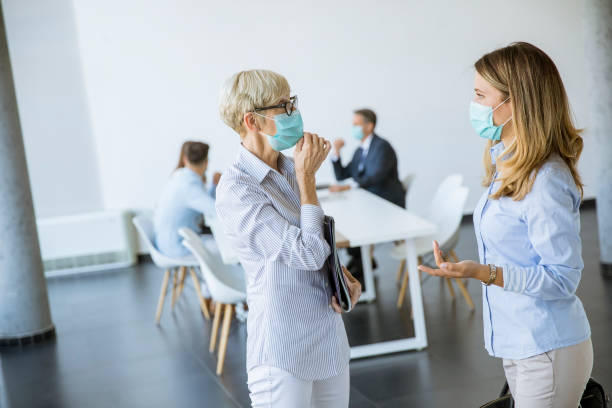 Two businesswomen talking in the office and wearing mask as a virus protection stock photo