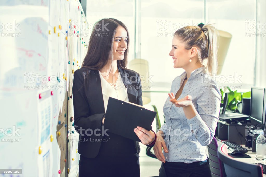 Two businesswomen talking to each other in the office. stock photo