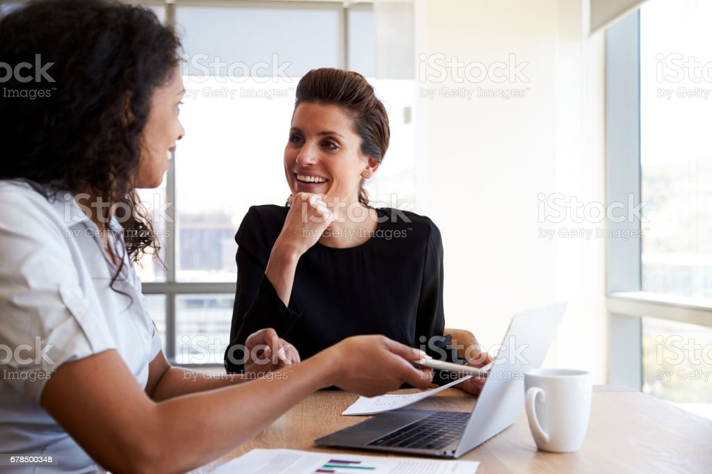 Two Businesswomen Using Laptop Computer In Office Meeting foto stock royalty-free