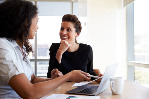 two businesswomen using laptop computer in office meeting - two people stock photos and pictures