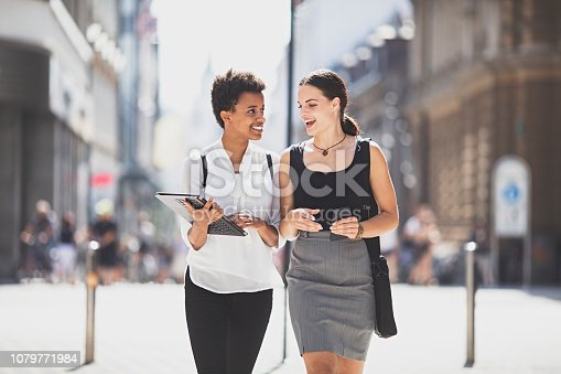 two businesswomen walking on the city streets