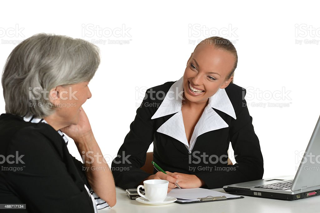 Two businesswomen with coffee and laptop stock photo