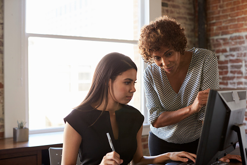 Two Businesswomen Working On Computer In Office Stock Photo - Download Image Now