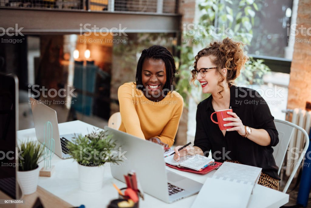 Two Businesswomen Working On Computer In Office - foto stock