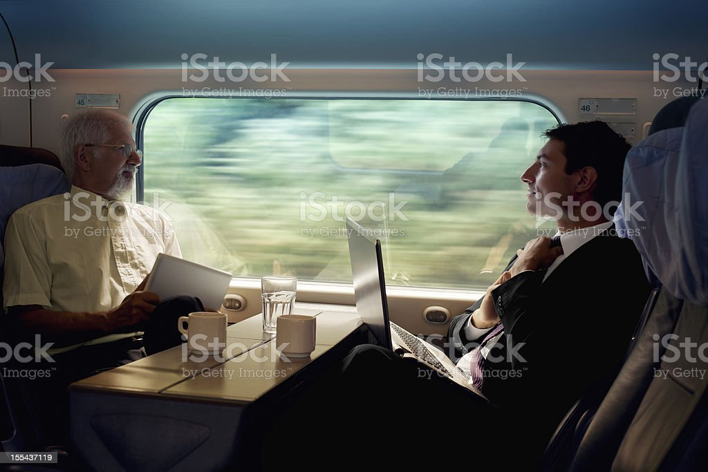 two bussinesman seating on a train   beside  window  and  working royalty-free stock photo