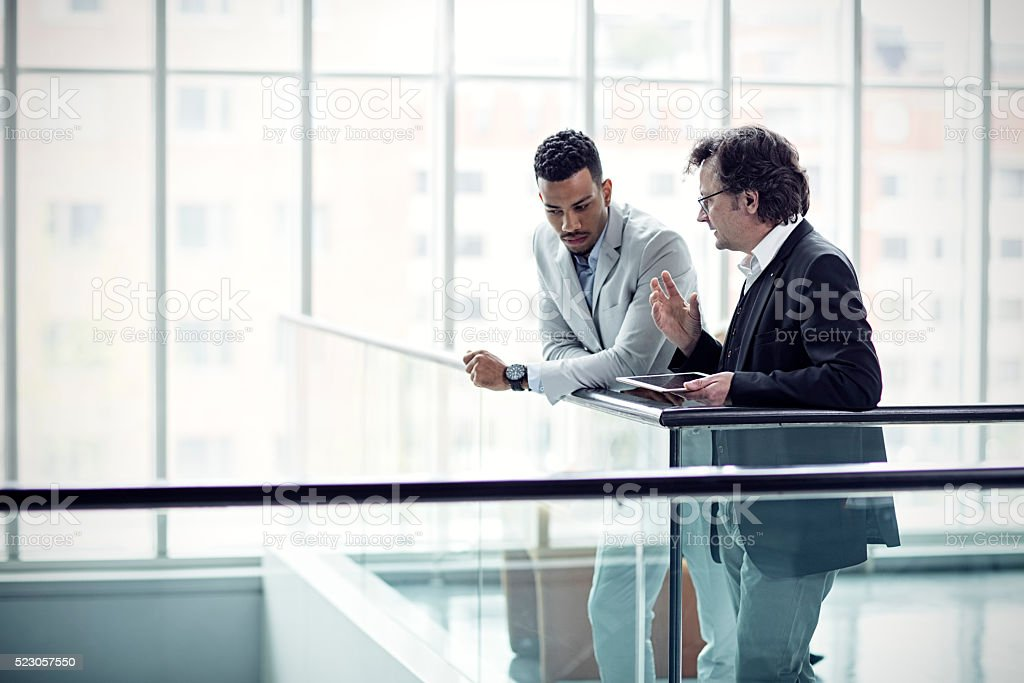 Two busuinessmen having a casual talk in hall stock photo