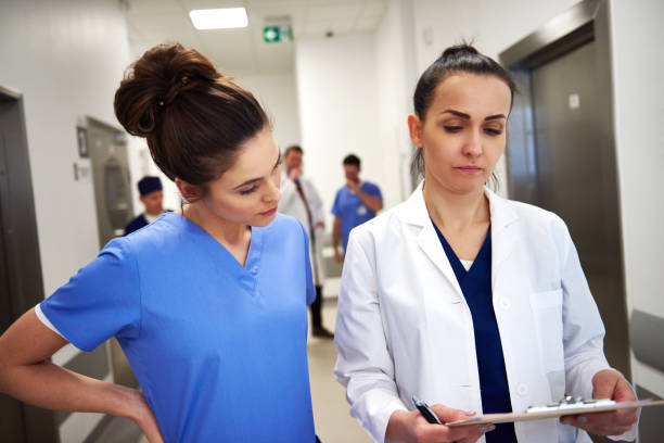 Two busy doctors discussing some medical records Two busy doctors discussing some medical records assistant stock pictures, royalty-free photos & images