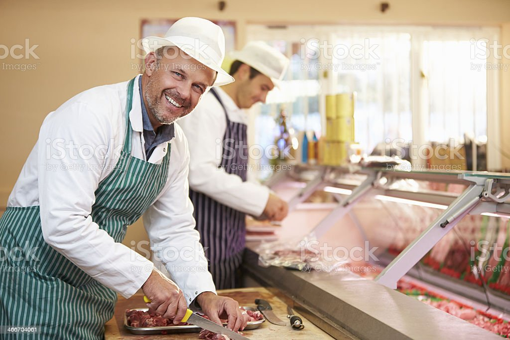 Two Butchers Preparing Meat In Shop stock photo