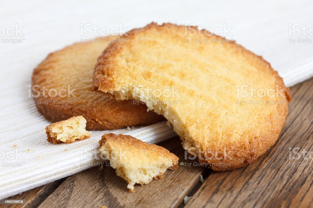 Two butter biscuits on napkin and wood. Broken. stock photo