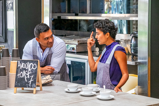 Two cafe owners/workers in conversation with woman making a point with finger, man is smiling: not serving customers, empty coffee/tea cups and saucers ready,
