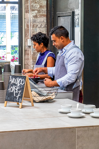 Two cafe owners/workers (small business), working behind counter preparing food & drinks: