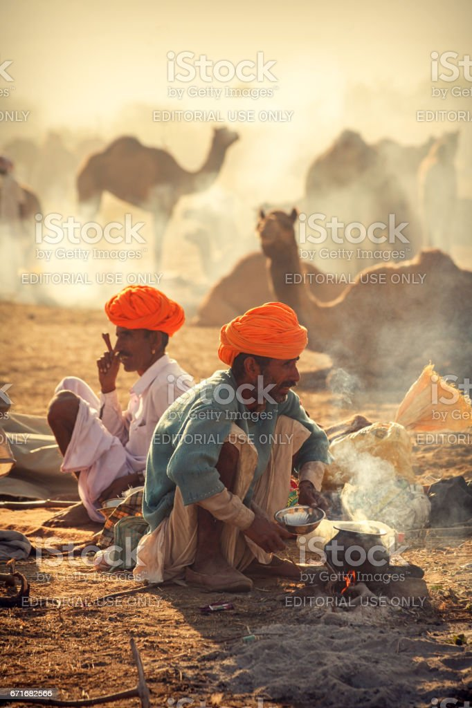 Two Camel herders involved in morning activities at Pushkar Camel Fair Place stock photo