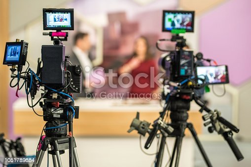Rear view of two cameras filming an infomercial TV-show.