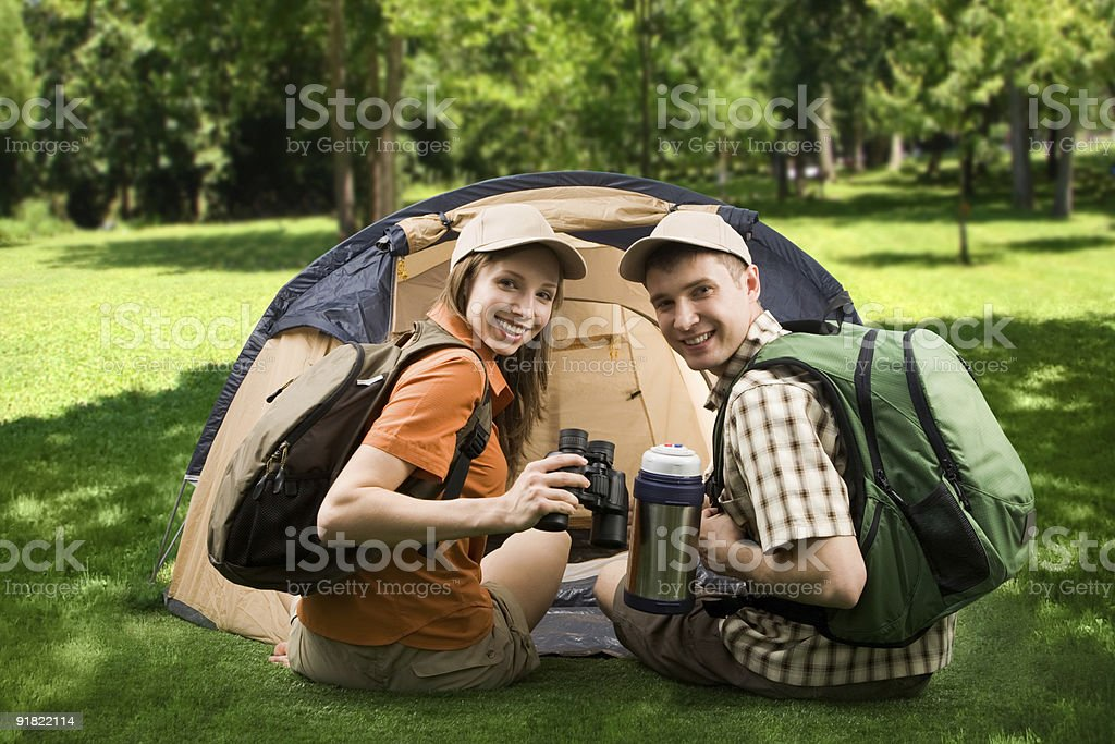 Two campers smiling for picture in front of tent royalty-free stock photo
