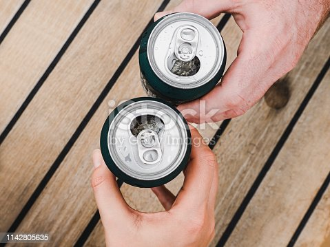 istock Two can of beer, female and male hands 1142805635