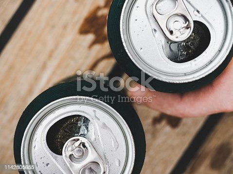 istock Two can of beer, female and male hands 1142805655