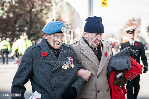 istock Two Canadian Army war veteran, senior men, with their medals and remembrance poppy, paying respects to dead soldiers on Remembrance Day 1147002368