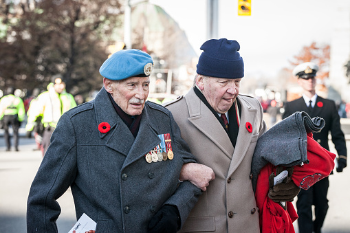 Two Canadian Army war veteran, senior men, with their medals and remembrance poppy, paying respects to dead soldiers on Remembrance Day