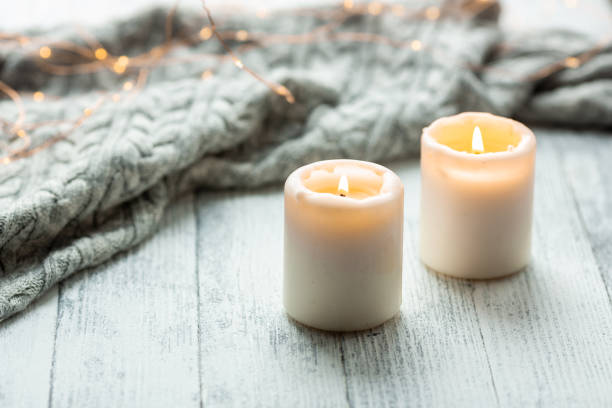 two candles sweater wooden table lights garland - candle stock pictures, royalty-free photos & images