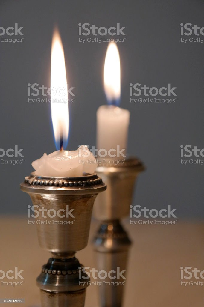 Two candlesticks with burning candles stock photo