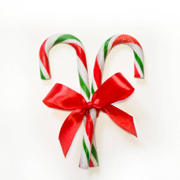 Two candy canes with red bow on white background. Two candy canes with red bow on white background. Square image. candy cane stock pictures, royalty-free photos & images