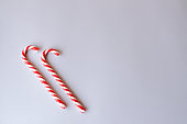 Two cane candies on a gray background.