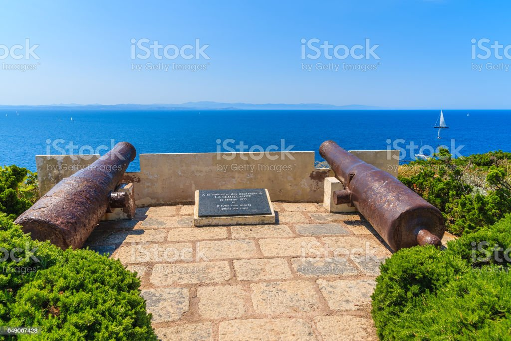 Two cannons on coast of Corsica island in Bonifacio town, stone grave says 'in memory of the officers of the armies of land and stock photo