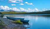 Two blue canoes on the shore of a calm lake with green hills in background