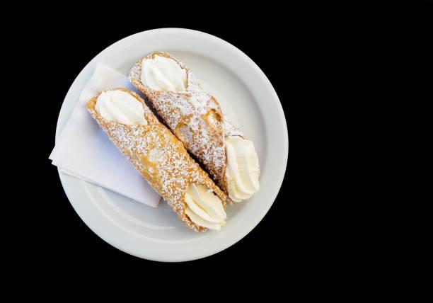 auf einen teller gelegt zwei canoli mit buttercreme über schwarzen hintergrund - cannoli stock-fotos und bilder