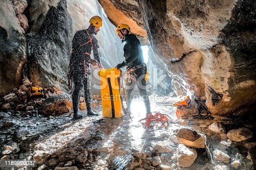 Two canyoneering climbers gathering their climbing rope into a waterproof sturdy bag at the bottom of a gorge.