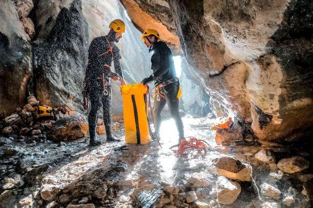Zwei Canyoneer packen ihr statisches Seil in einen wasserdichten gelben Sack am Canyonboden – Foto