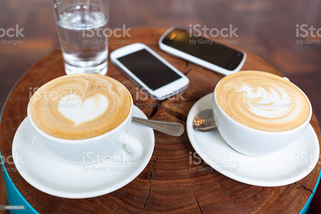 Two cappuccino and smart phones on a table in cafe stock photo