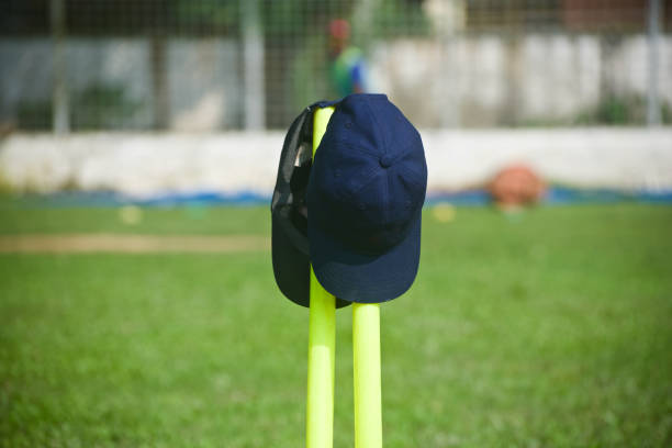 Two caps kept on the cricket stumps in a field stock photo