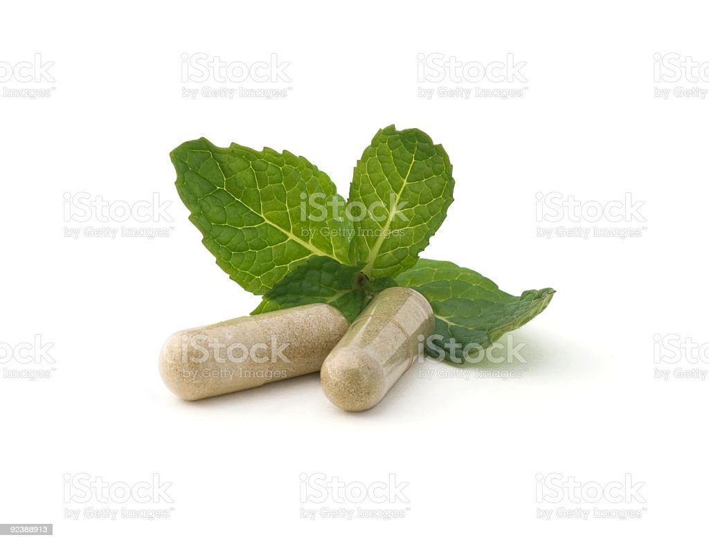 Two capsules and leaves of herbal medicine on white surface stock photo