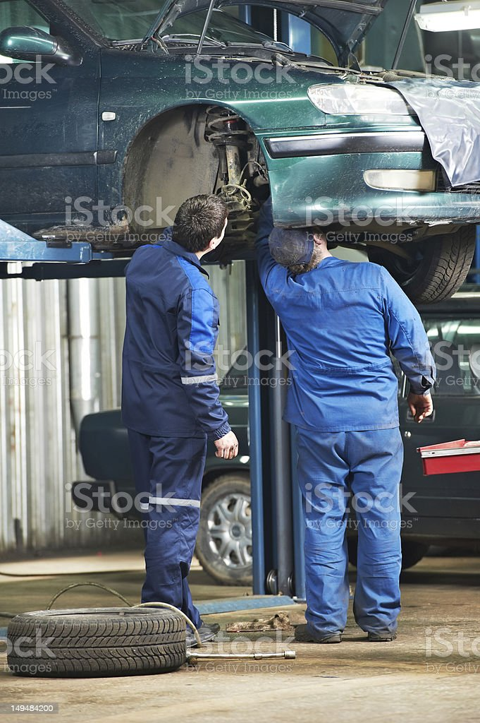 two car mechanic diagnosing auto suspension stock photo