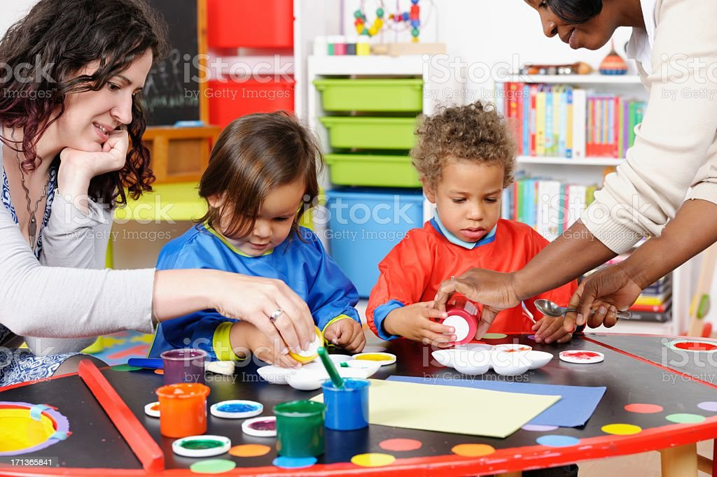 Two Carers/ Teachers Supervising Little Boys During Art And Craft stock photo