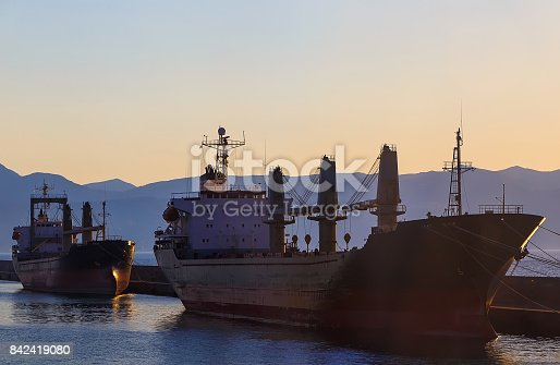 istock Two cargo ship in port of Heraklion City at sunset and the mountains. Greece. 842419080