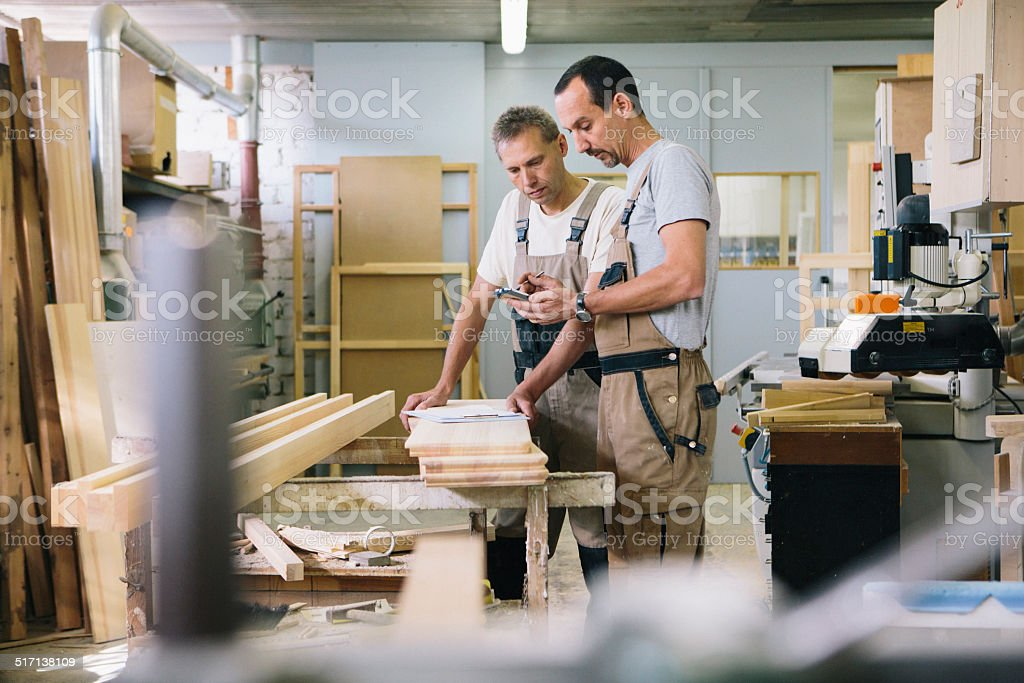 two carpenter using smart phone for planning stock photo