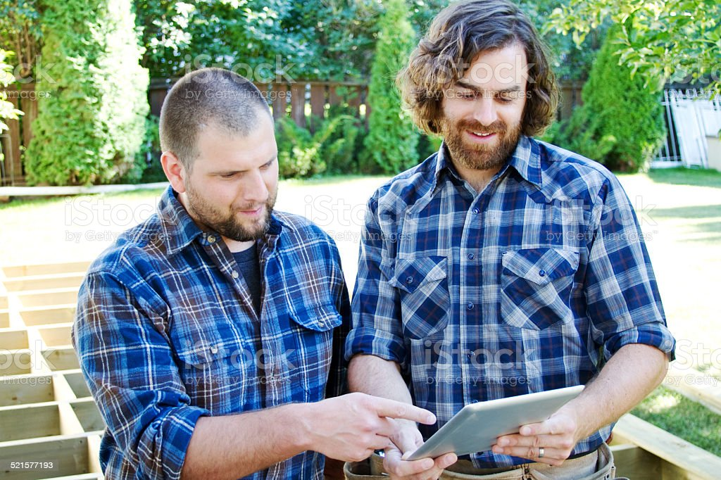 Two carpenters planning on tablet stock photo