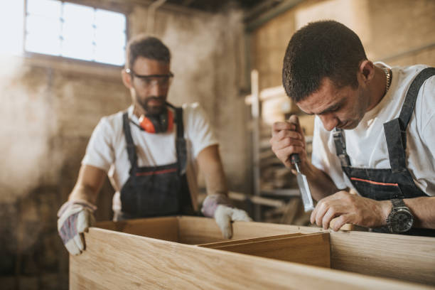 Two carpenters working on a piece of furniture in a workshop. stock photo