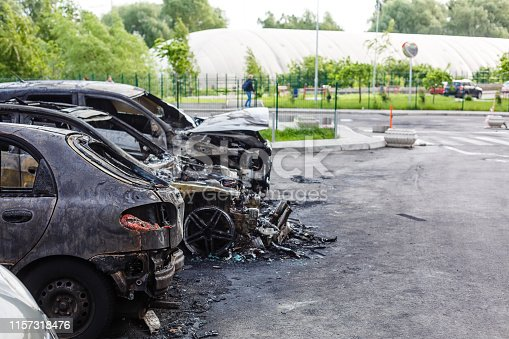 istock Two cars after the fire. Two burned out cars with an open hood. Arson, burnt car 1157318476