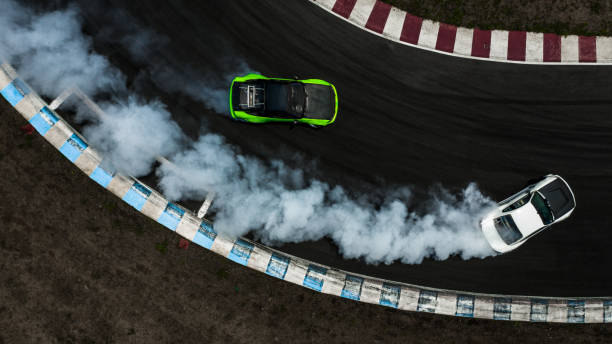 two cars drifting battle on race track with smoke, aerial view two car drifting battle. - burnout стоковые фото и изображения
