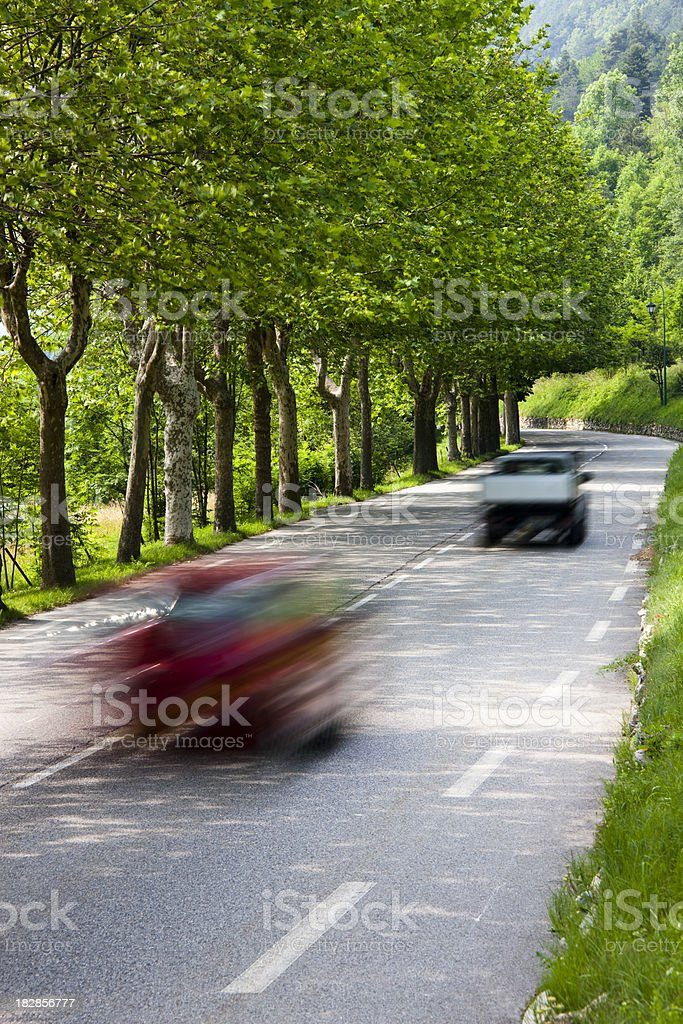 Two Cars Driving Down Country Road Through Spring Mountain royalty-free stock photo