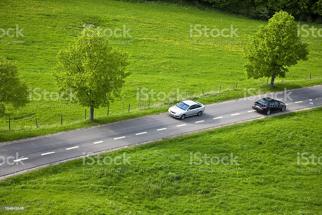 Two Cars Driving Fast on Country Road stock photo