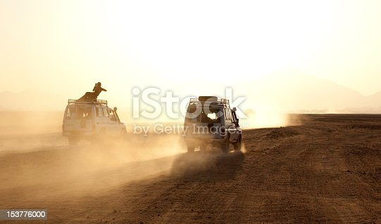 istock Two cars kicking up dust on a desert safari 153776000