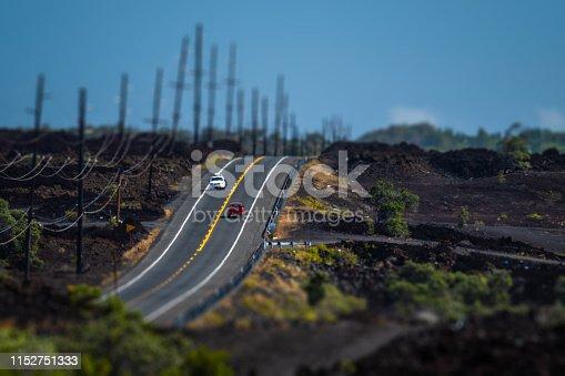 Two cars meet on the Mamalahoa Highway (Hawaii Belt Road) in Kau district with black lava fields around. Hawaii, USA