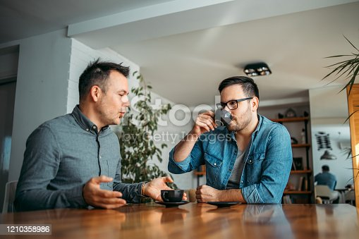 Two casual businessmen talking and drinking coffee at workplace, portrait.