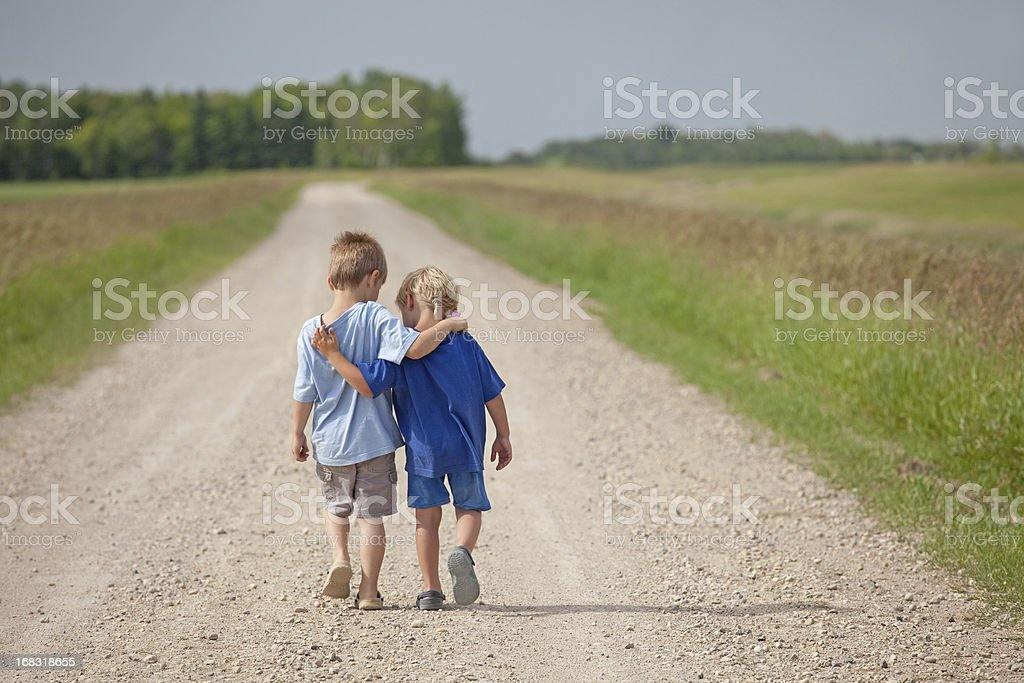 Two Caucasian Boys Walking Down a Country Road Two young boys walking arm in arm down a rural country gravel road. Prairie scene. Elementary aged caucasian children. Horizontal color image. Additional themes include friendship, bonding, boys, embracing, hugging, love, relationships, brothers, kindergarten, preschool, talking, care, best friends, and summer.  4-5 Years Stock Photo
