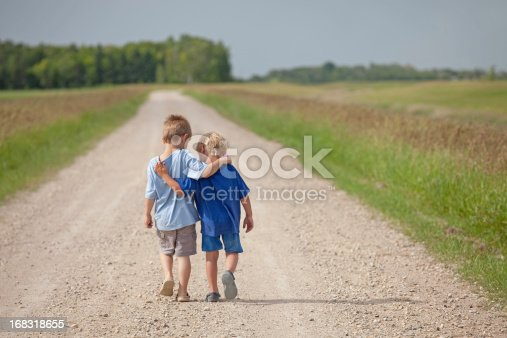 Two young boys walking arm in arm down a rural country gravel road. Prairie scene. Elementary aged caucasian children. Horizontal color image. Additional themes include friendship, bonding, boys, embracing, hugging, love, relationships, brothers, kindergarten, preschool, talking, care, best friends, and summer.